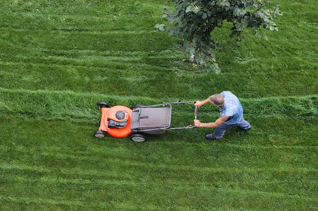 Man cuts the lawn. lawn mowing. aerial view lawn mower on green grass Premium Photo