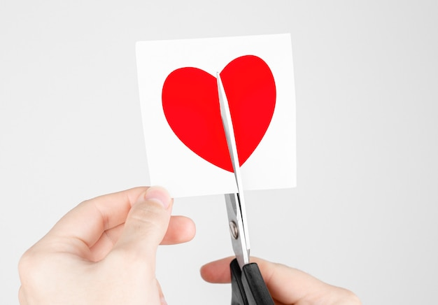 Man cuts scissors sticker with red heart Premium Photo