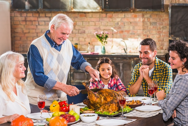 Man cutting baked chicken at table with family Free Photo