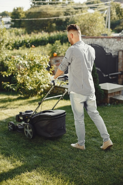 Man cutting grass with lawn mover in the back yard. male in a shirt. Free Photo