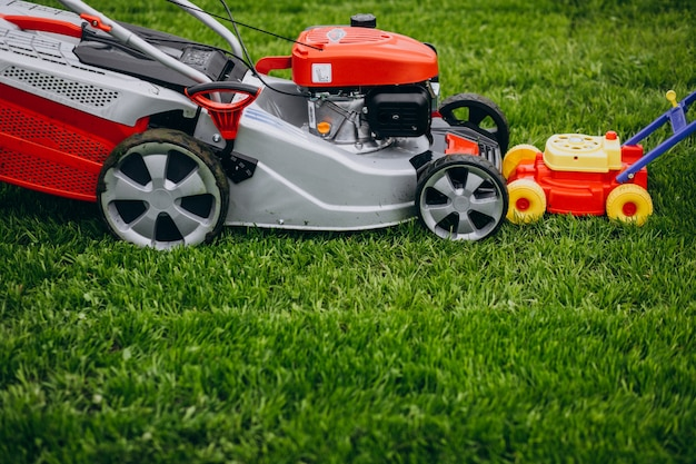Man cutting grass with lawn mover in the back yard Free Photo