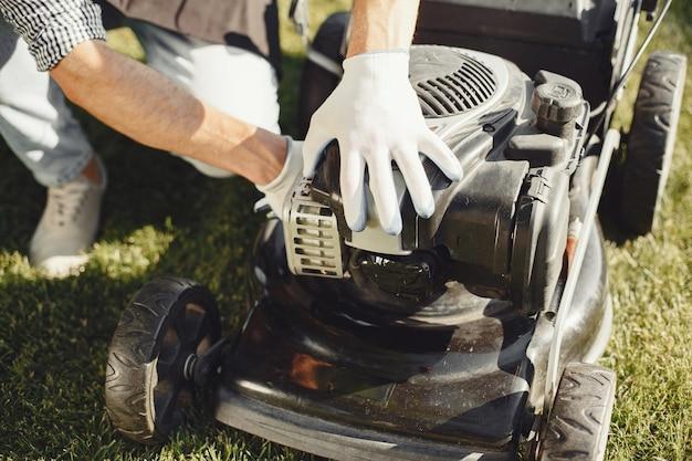 Мужчина косит траву газонокосилкой на заднем дворе. мужчина в черном фартуке. парень ремонт. Бесплатные Фотографии