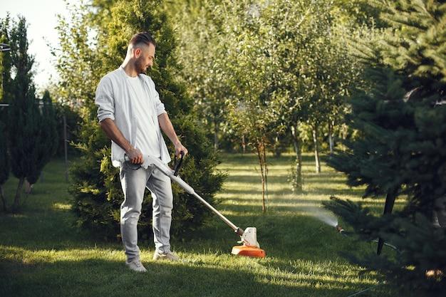 Мужчина косит траву газонокосилкой на заднем дворе. мужчина в рубашке. Бесплатные Фотографии