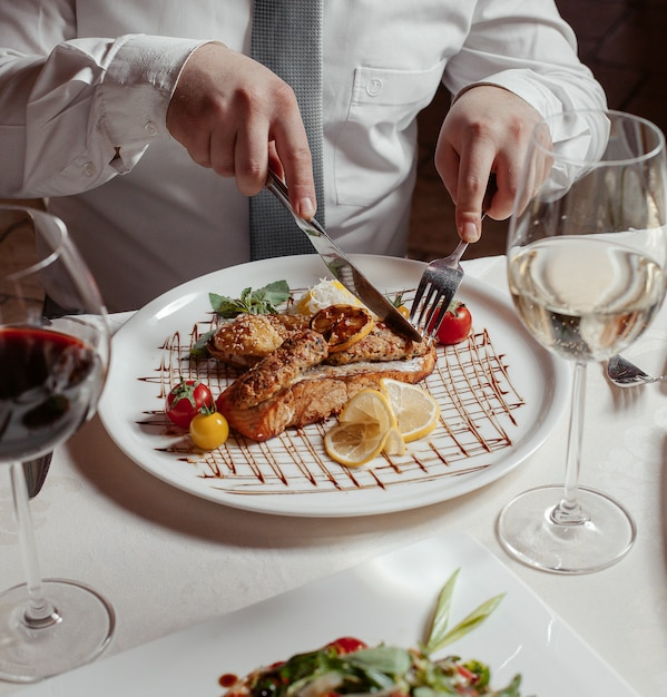 Man cutting grilled salmon served with rice, lula kebab, lice, tomatoes, wine Free Photo