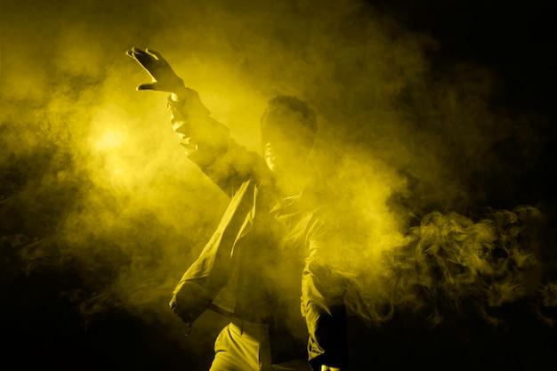 Человек танцует в дыму с освещающим светом Бесплатные Фотографии