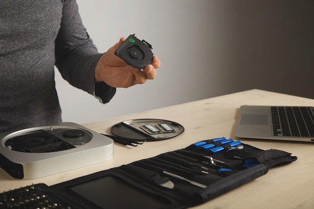 A man in a dark gray t-shirt looks at a cooler he took out of a computer, his tools in front of him on the table Free Photo