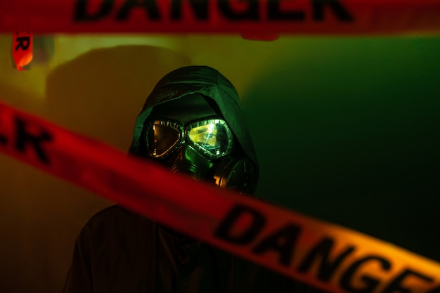 A man in a dark protective suit with a gas mask on his face and a hood on his head posing standing near a green wall with danger tapesdanger Premium Photo