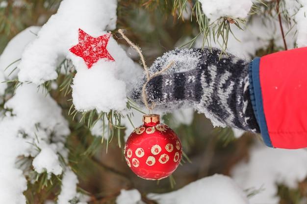 Мужчина украшает елку в зимнем лесу Premium Фотографии