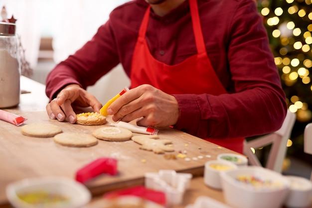 Uomo che decora i biscotti in cucina Foto Gratuite