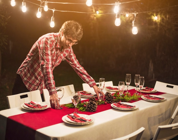 Man decorating table with baubles for party Free Photo
