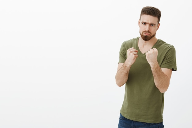 Man determined to fight calories after holidays. portrait of handsome serious-looking angry bearded guy in t-shirt frowning making scary face as holding fists like boxer wanting punch and beat person Free Photo