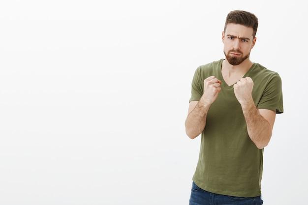 男は休暇後にカロリーと戦うと決心した。パンチとビートの人を望んでいるボクサーのような握りこぶしを握っているので怖い顔をしてtシャツのしかめ面でハンサムな深刻な怒っているひげを生やした男の肖像 無料写真