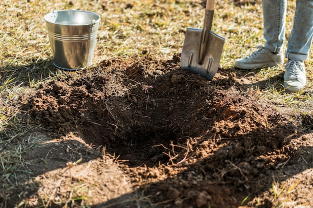 Man digging a hole with shovel to plant a tree Free Photo