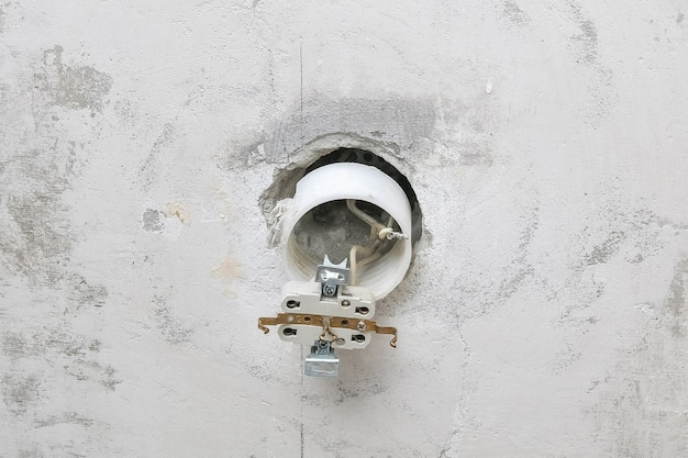 A man dismantles and mends an electrical outlet for repairs. power socket. Premium Photo
