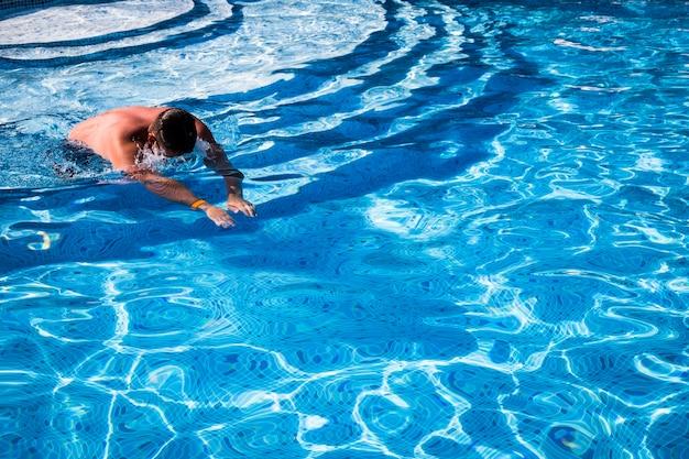 男は青い水でプールに飛び込む Premium写真