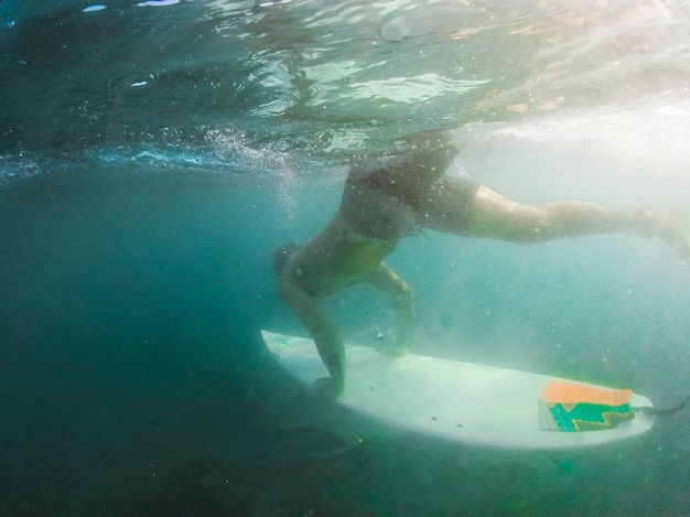 Man diving with surfboard underwater Free Photo