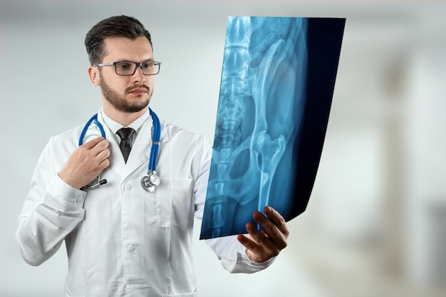 A man, a doctor in a white coat, carefully looking at the picture Premium Photo