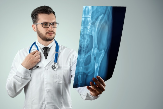 A man, a doctor in a white coat, carefully looking at the picture. Premium Photo