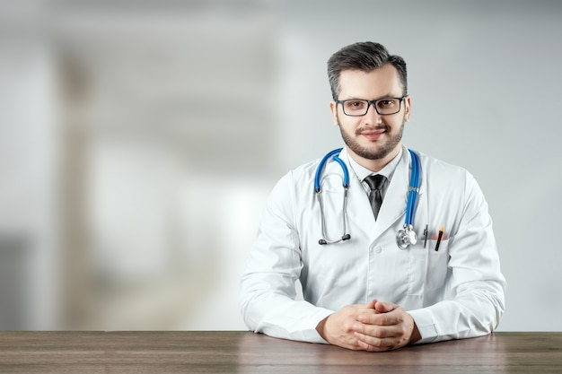 A man, a doctor in a white coat with a stethoscope Premium Photo