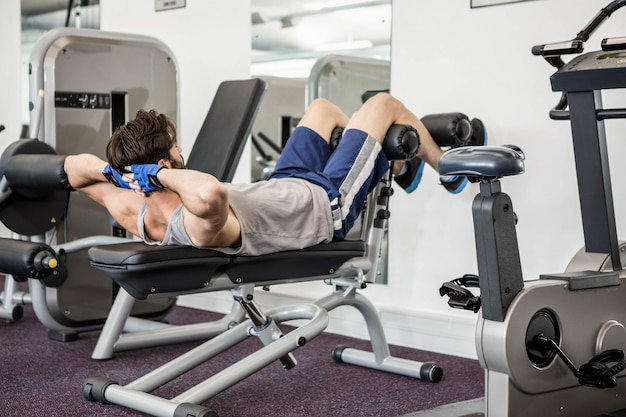 Man doing abdominal crunches on bench at the gym Premium Photo