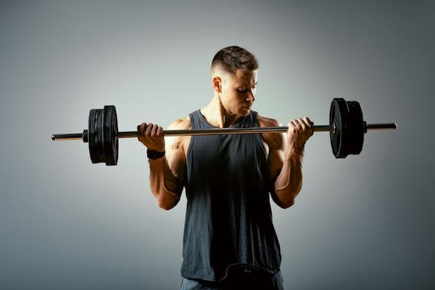 Человек делает обратно тренировки, ряд штанги в студии на сером фоне. Premium Фотографии