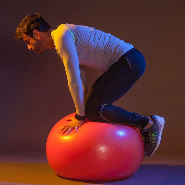 Man doing balance exercise on fitness ball 23 2147776464