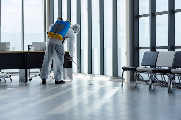 Man doing disinfection at office Premium Photo