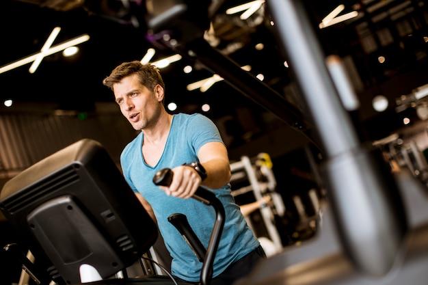 Man doing exercise on elliptical cross trainer in sport fitness gym club Premium Photo