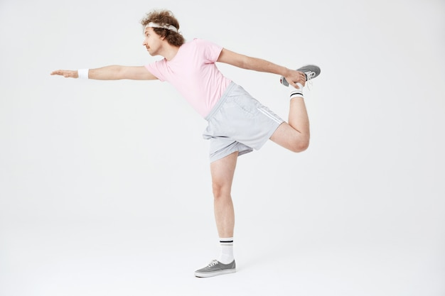 Man doing horizontal position on one leg with hand up Free Photo