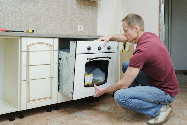 Man doing the installation of the built-in electric oven. Premium Photo