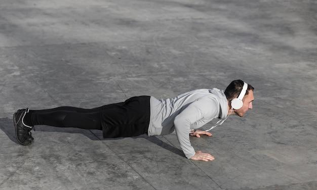 Man doing push ups and listening music Free Photo