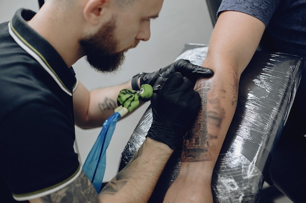 Man doing a tattoo in a tattoo salon Free Photo