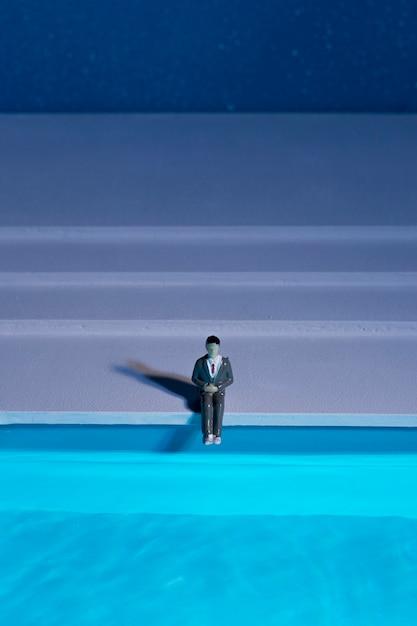 Bambola uomo seduto accanto alla piscina Foto Gratuite