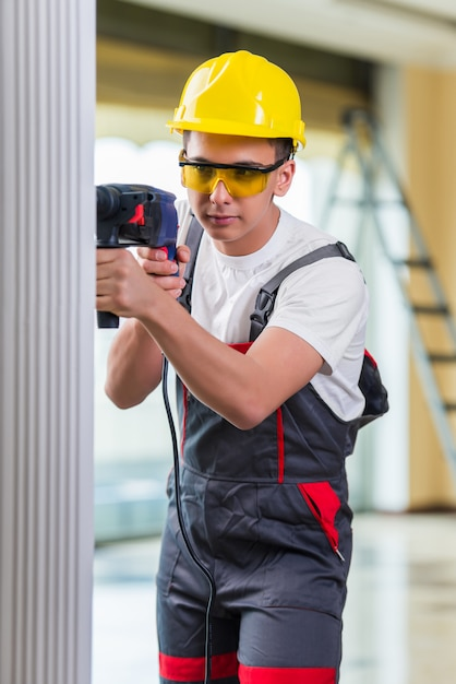 Man drilling the wall with drill perforator Premium Photo