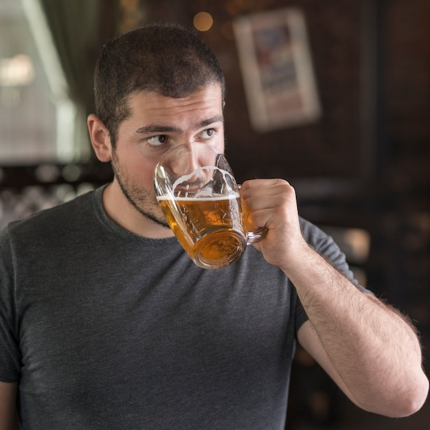Man drinking beer and looking away Free Photo