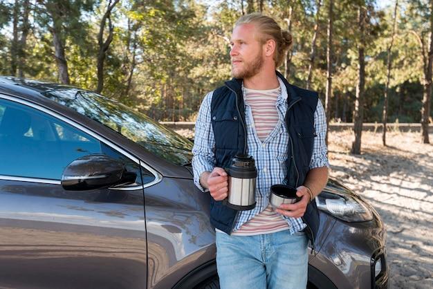 Uomo che beve caffè e guarda lontano Foto Gratuite
