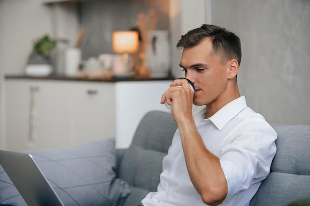 自宅のソファでリラックスしてコーヒーを飲む男 Premium写真