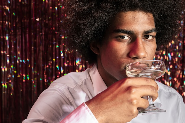 Man drinking a glass of champagne with curtain of sparkles in background Free Photo