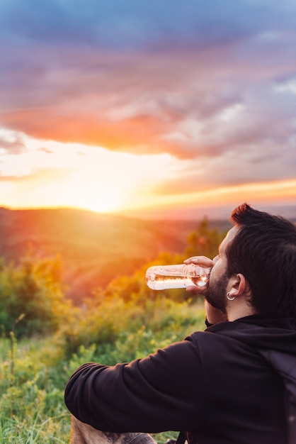 Man drinking water and enjoying mountain sunset Premium Photo