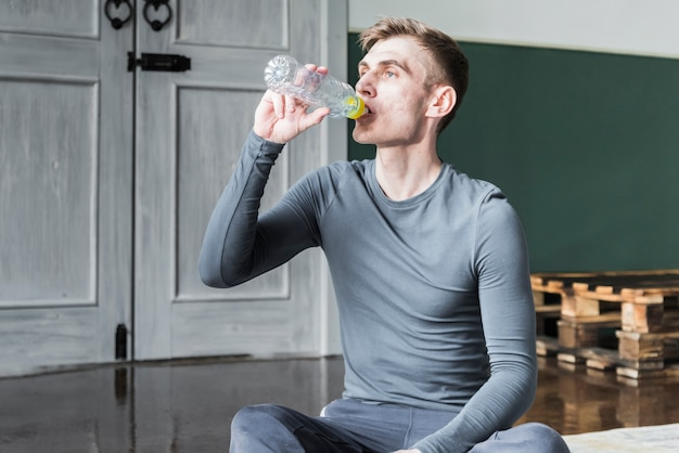 Man drinking water from bottle sitting on floor Free Photo