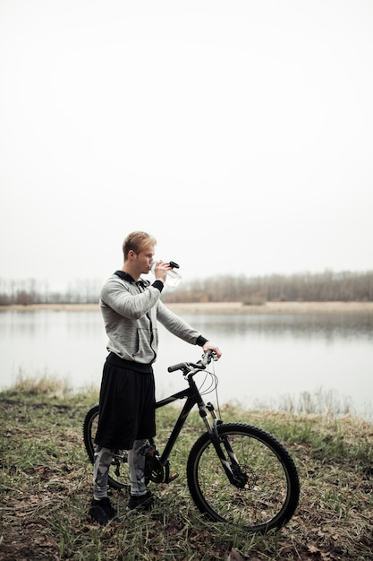 Man drinking water from bottle standing with bicycle near the pool Free Photo