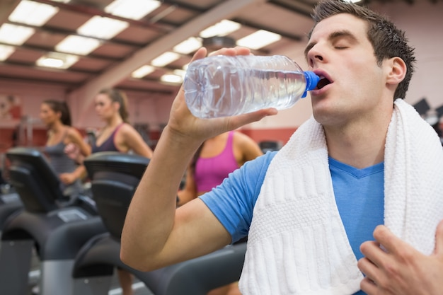 Man drinking water in the gym with towel around neck photo man drinking water in the gym with towel around neck premium photo sciox Choice Image