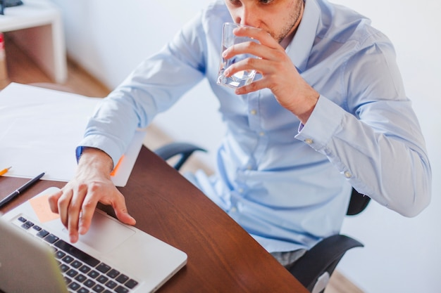 Man drinking water sitting at table Free Photo