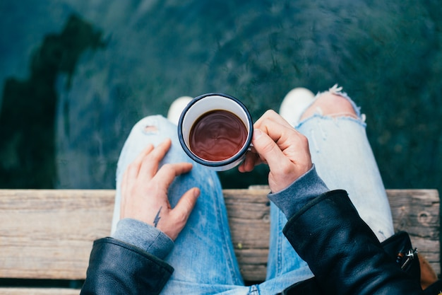 Man drinks coffee from enamel cup outdoors Free Photo
