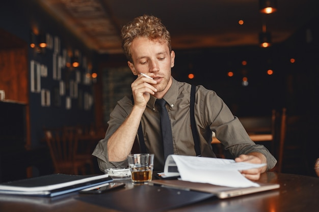 Man drinks whiskey. businessman reads documents. director in a shirt and suspenders. Free Photo