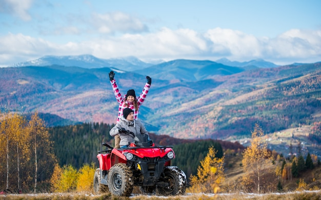 Man driving atv quad bike, woman sitting behind him and raised her hands up on a mountain road Premium Photo