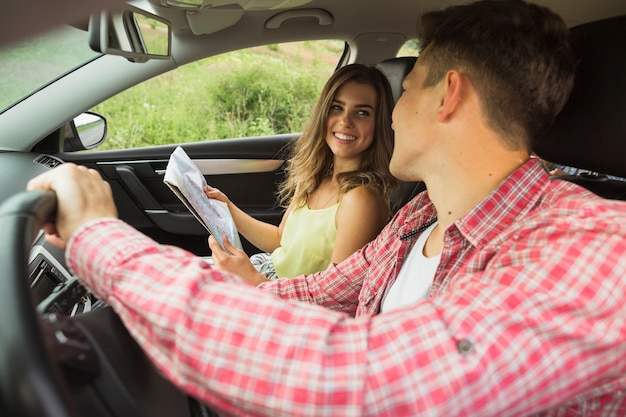 Man driving the car looking at woman holding map Free Photo