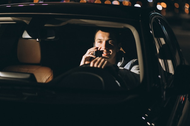 Man driving a car on the road and talking on the phone Free Photo