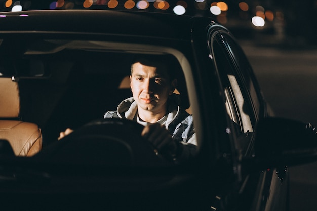 Man driving a car on the road Free Photo