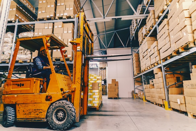 Man driving forklift in warehouse. all around shelves and boxes. Premium Photo